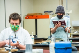 two students in the lab with masks, on of the reading a book